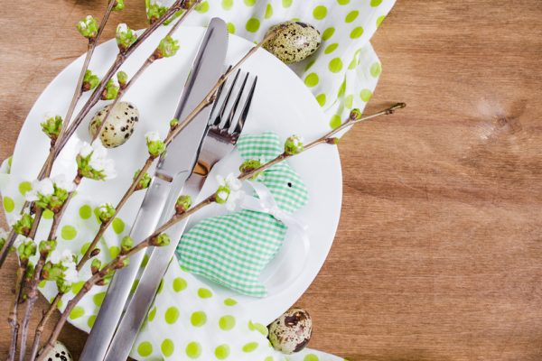 Festive table setting for Easter dinner with spring flowers and cutlery on wooden rustic table. Selective Focus.