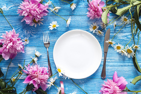 Festive table setting with cutlery, peonies and daisies on blue wooden background. Top view.