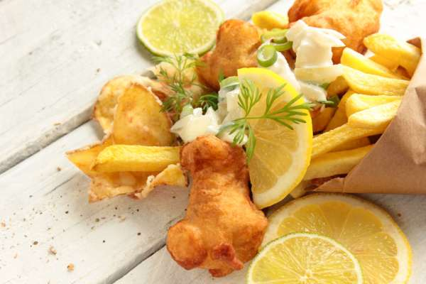 Backfisch Pommes Kartoffelchips Fish and Chips Tüte Tisch